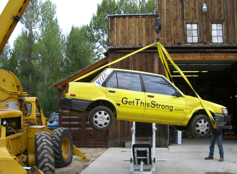 This is the crane that was used to place the Toyota on the leg press. You can see how the front strap dented the fender.